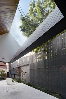 A breezy patio features a pitched roof that offers a view of the sky.
