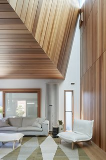 A Ligne Roset Callin Lounge Chair and footstool from Domo Australia offer comfort and softness within the soaring angles of the interior.