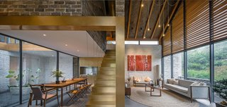 The dining and living areas are separated by a suspended, copper-plated staircase.