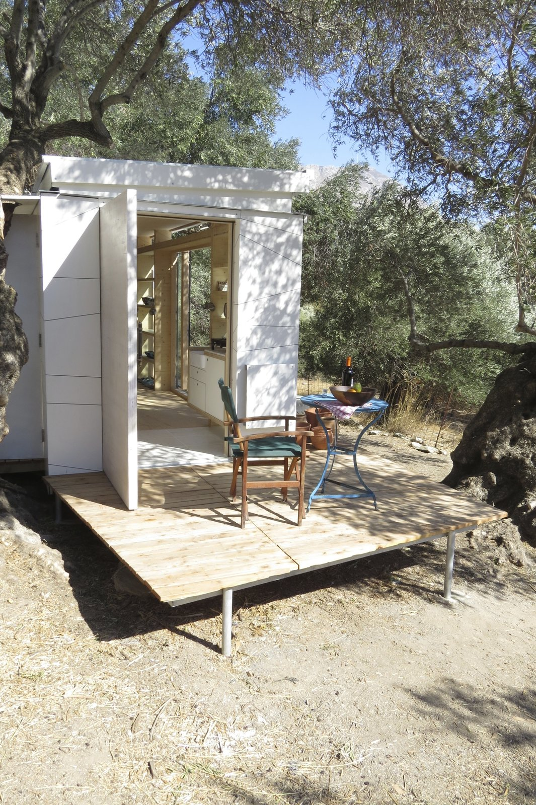 Outdoor, Side Yard, Small Patio, Porch, Deck, Trees, Wood Patio, Porch, Deck, and Decking Patio, Porch, Deck The large external door to the end of the house is solid timber.  Photo 1 of 10 in A Yoga Teacher's Tiny Home on Wheels Goes Off-Grid in Greece