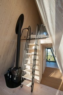 A wood-burning stove squats by the ladder that leads to the sleeping loft. Electrical heating are incorporated into the wood floors.