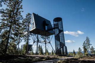 A spiral staircase, inspired by fire lookout towers, leads up to the A-frame cabin.