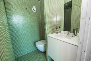 The bathroom is lined in green mosaic tiles.