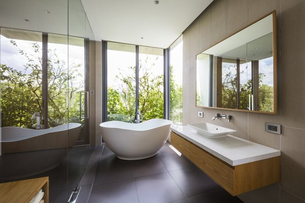 A freestanding tub, placed near a window, enjoys a green view as well as privacy.