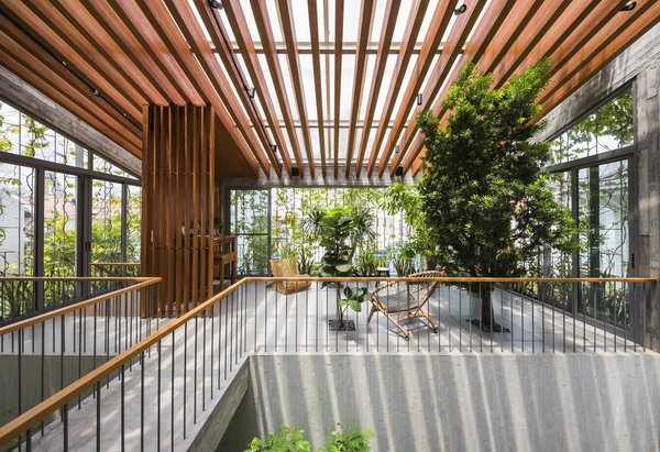 The family lounge area lies under a wooden, louvered ceiling that provides shade while still allowing ample sunlight to stream into the home.
