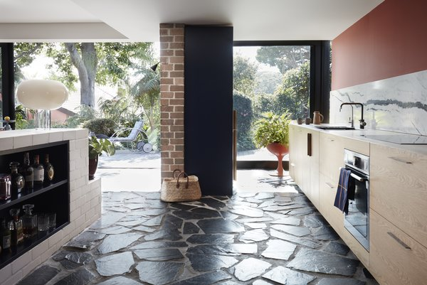 A brick plinth serves as a kitchen island. Below lies an integrated mini bar.