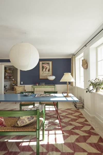 A colorful table by Muller van Severen stretches across the living space. In the background hangs a Picasso exhibition poster.