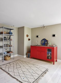 A red kitchenette by Københavns Møbelsnedkeri dominates the space, tempered by a more neutral Beni Ouarain rug. The storage rack in lavender is by HAY.