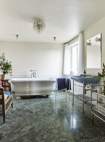 Green Swedish marble floors add a luxe touch to the bathroom. The small, vintage polydrone chandelier in clear glass is from The Apartment.