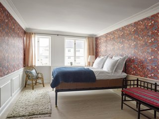 More Marthe Armitage wallpaper, this time in a bold, red floral print, graces this bedroom. A vintage Moroccan runner continues the dot pattern, and is paired with a vintage bench, and a rattan chair and pillow from The Apartment.