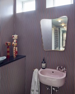 A brass mirror and Japanese Kokeshi dolls add whimsical, vintage touches in contrast to the wallpaper by Helene Blanche of Tapet Café.