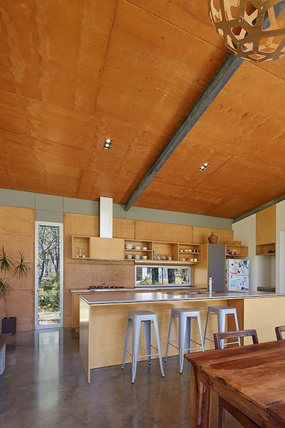 At sunrise, light bounces off the rammed earth wall, imbuing the kitchen with a warm, orange glow at breakfast.