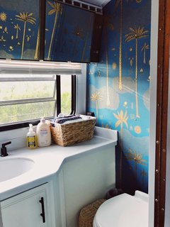 The bathroom walls feature Justina Blakeney Cosmic Desert Wallpaper from Hygge & West.