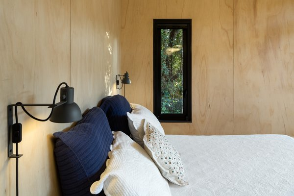 A slender window in the bedroom looks out to the trees.