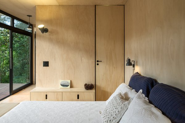 A compact closet blends in with the plywood walls.