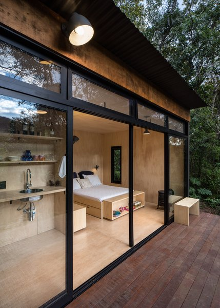 Located in a forested, countryside area near a lake and vegetable garden, the cabin was designed by São Paulo architect Silvia Acar as a simple space for sleeping, cooking, and reconnecting with nature.
