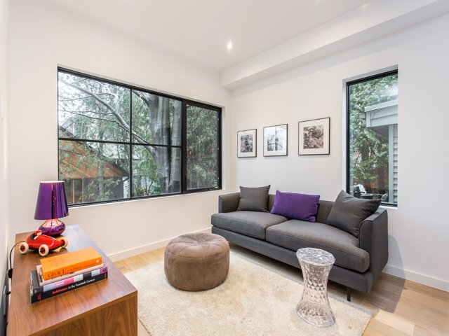 The family room, adjacent to the kitchen, features views on a private garden.   Manor Road house