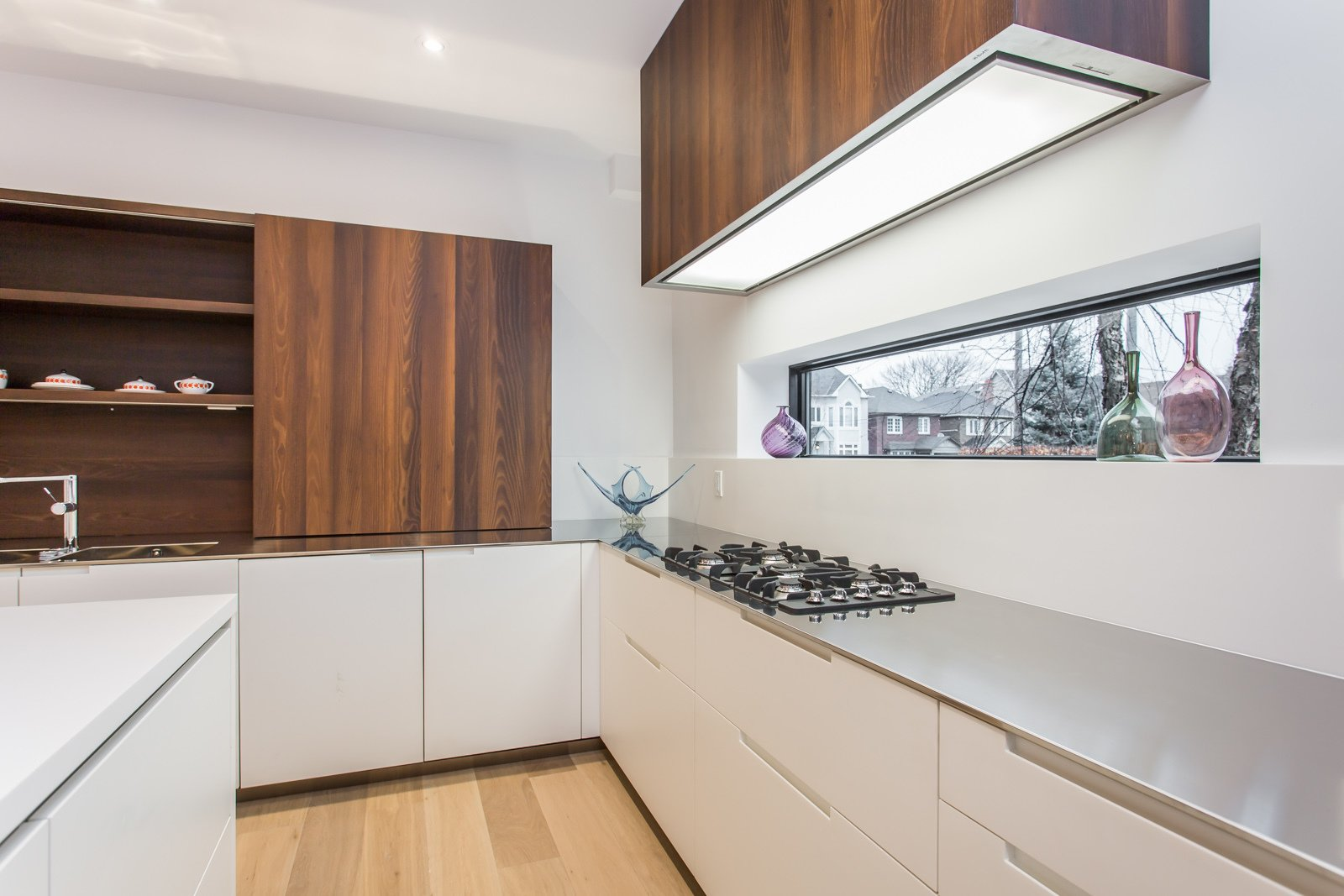 A long window above the countertop provides a nice view to the outside world while cooking.   Manor Road house