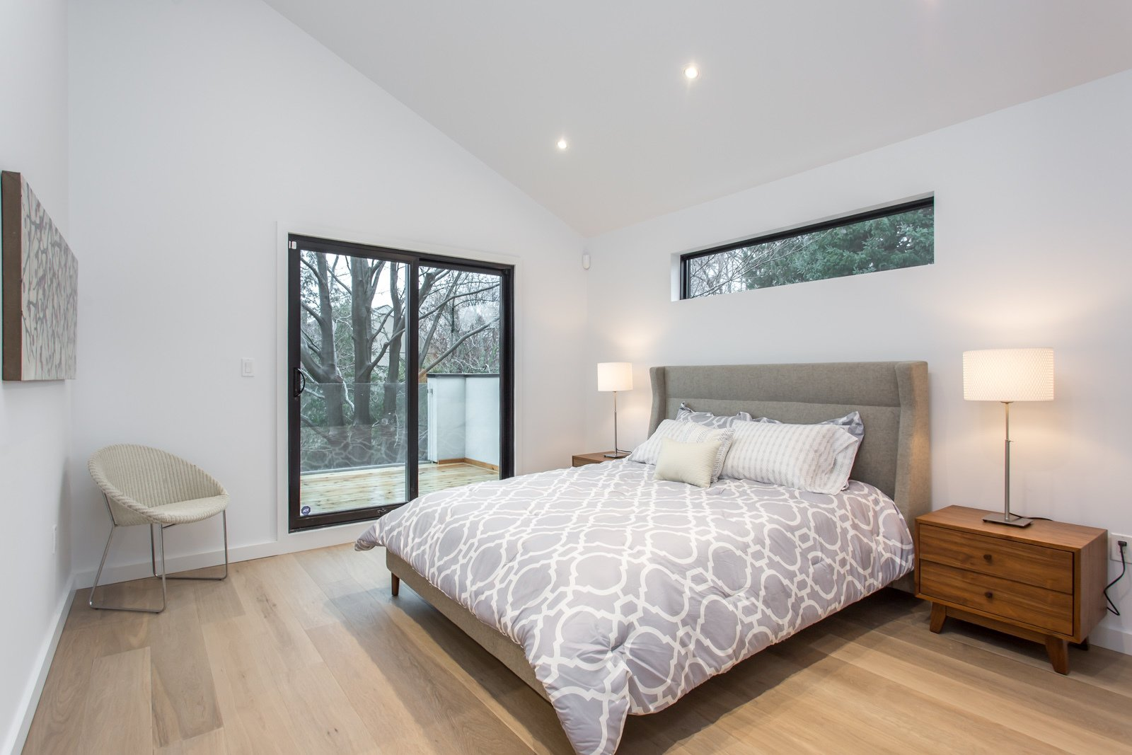 The master bedroom on the second floor with a walk out deck, overlooking the private backyard.   Manor Road house