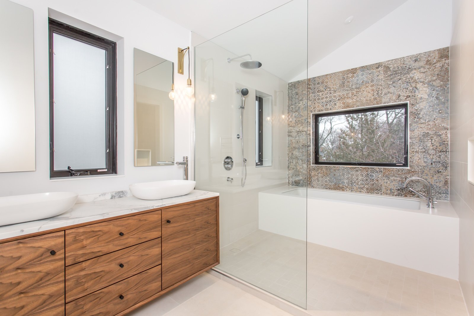 A master ensuite, with a bath/shower area, Vestige pattern tiles from Aparici, marble countertop and a walnut vanity.   Manor Road house