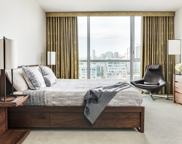 Bed, nightstands and dresser in walnut by DWR. Holly Hunt lights throughout. Metropolitan Lounge chair and ottoman by B&B Italia. Bentley carpet, wallcovering by Graham & Brown and drapery from Rodolph. Bedding and throw from Yves Delorme.