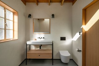 "The bathroom of a Tucson territorial-style midcentury features tadelakt walls done by a talented local craftsman and Neolith floors. The tub, from Blu Bathworks, sits on a Douglas fir base, so as to look as though it's floating. Douglas fir wood was used to match the original wood in the home. ""Similar to the rest of the home, we wanted to keep the space minimal and austere in design, yet highly functional,"" says architect Darci Hazelbaker. ""With the additional square footage gained from the closets, our intention was to allow that additional space to stay 'empty.'"""