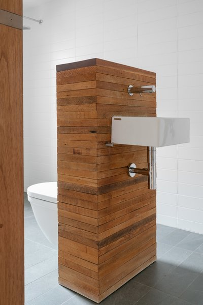 """A central pedestal holds both the wall-hung toilet and sink to save on space. """"We wanted the bathroom to feel open and easy for two people to move around in if we both happened to be in there at the same time,"""" says Dale."""