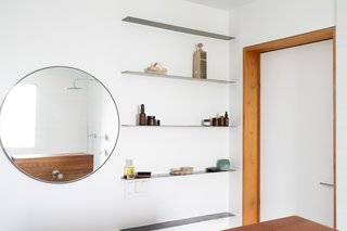 Opposite the sink, steel shelving adds storage with a minimal profile.