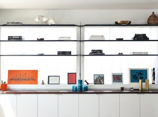 Custom steel shelving runs in front of two large windows in the bedroom. The designers wanted to keep a thin profile to avoid blocking natural light.