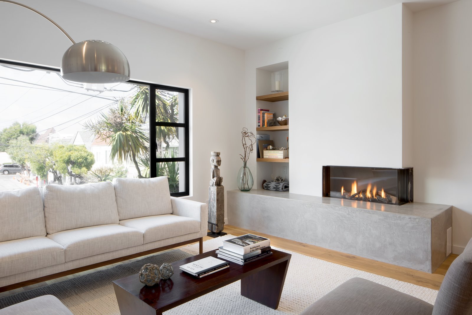 Living room Tagged: Living Room, Sofa, Light Hardwood Floor, Coffee Tables, Corner Fireplace, Floor Lighting, and Gas Burning Fireplace.  27th Street - Noe Valley by patrick perez/designpad architecture