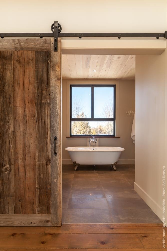 Main bathroom has a very warm feeling created by the raw elements used on the floors, walls and ceiling.  La Maison Hatley