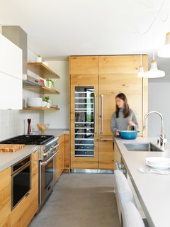 Red Dot Studio upgraded the Laidley Cottage kitchen with a wood-fronted refrigerator and cabinets, open shelving, and whimsical pendant lighting.