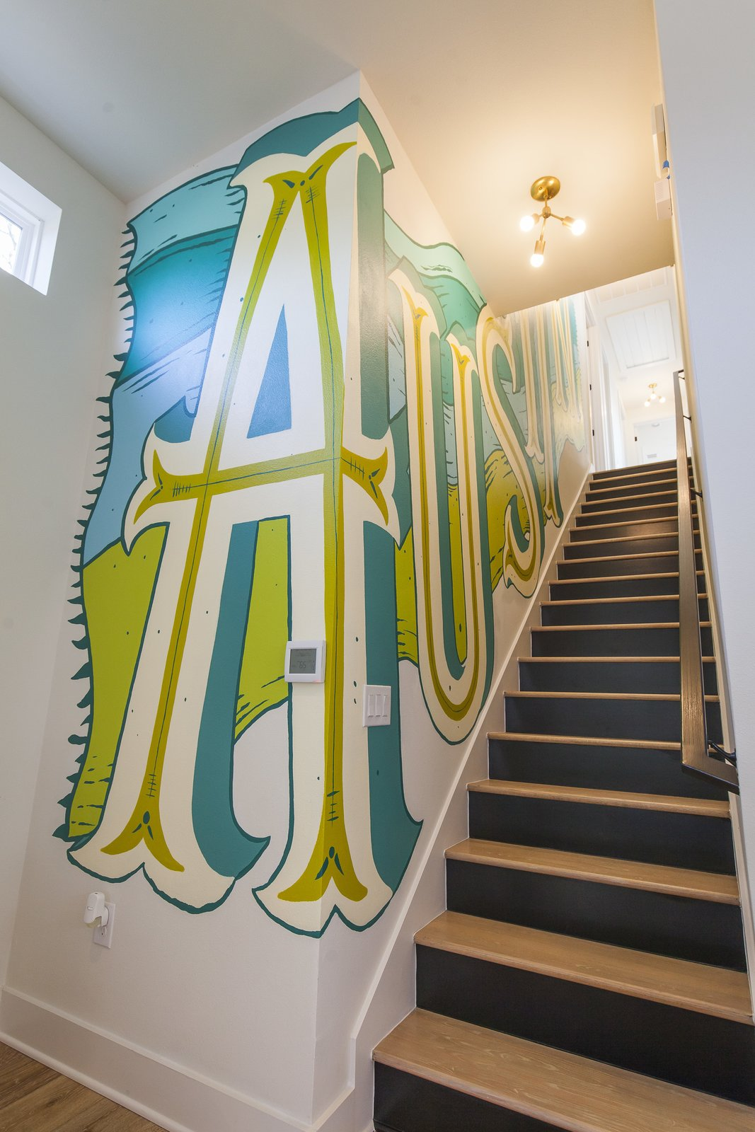 Staircase, Metal Railing, and Wood Tread Unit A - Stairwell - This is the custom mural we had designed for the staircase to keep things interesting but also invite some good ole' Austin charm into the house.  The Reyes Duplex