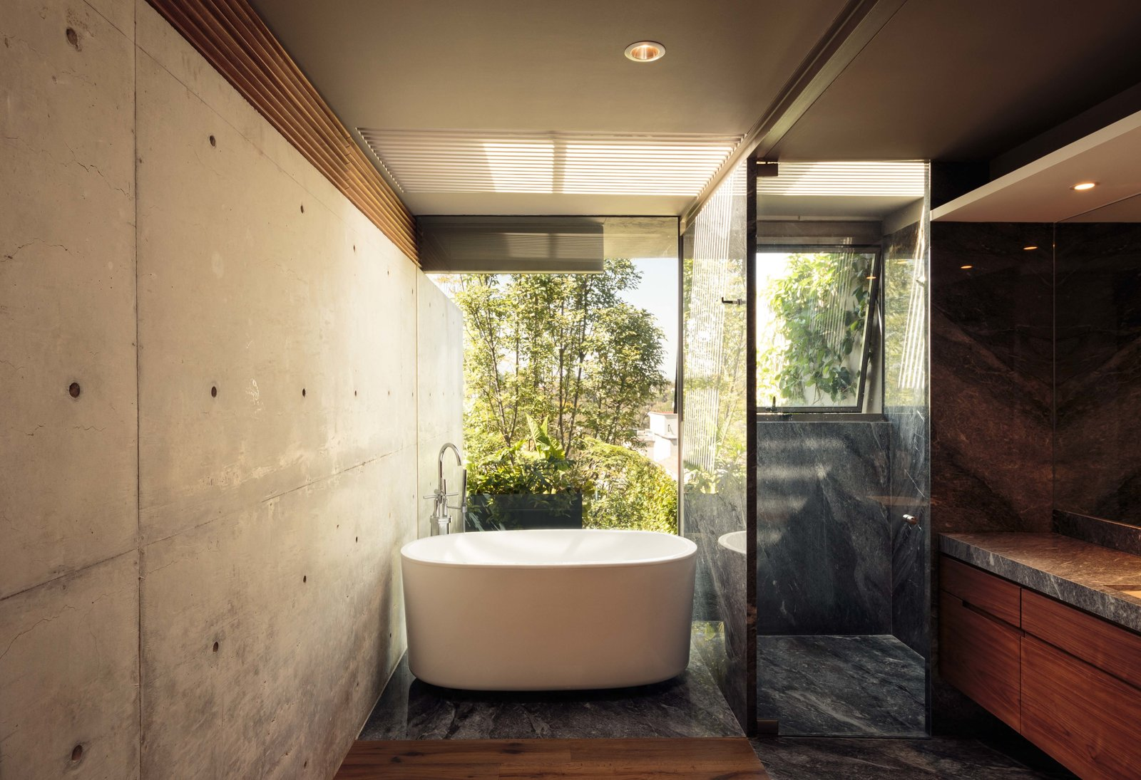 Bath Room, Granite Counter, Medium Hardwood Floor, Soaking Tub, Enclosed Shower, Freestanding Tub, Recessed Lighting, and Concrete Wall CAUCASO  Caucaso by Jose Juan Rivera Rio