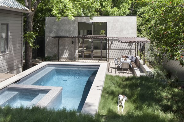 A grassy area provides a spot for sunning poolside, and a steel trellis shades an integrated dining area beyond