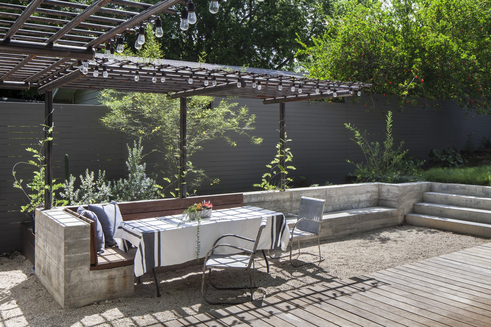 Outdoor, Wood Patio, Porch, Deck, Walkways, Grass, Trees, and Hanging Lighting New outdoor dining space is defined and by a custom concrete and wood bench with steel trellis above .  Garner Pool & Casita