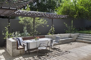 New outdoor dining space is defined and by a custom concrete and wood bench with steel trellis above .