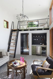 The new casita features a double-height living room with custom cement tiles and plaster walls, as well as a kitchenette nook, and custom steel & wood ship ladder to a sleeping loft above the bathroom.