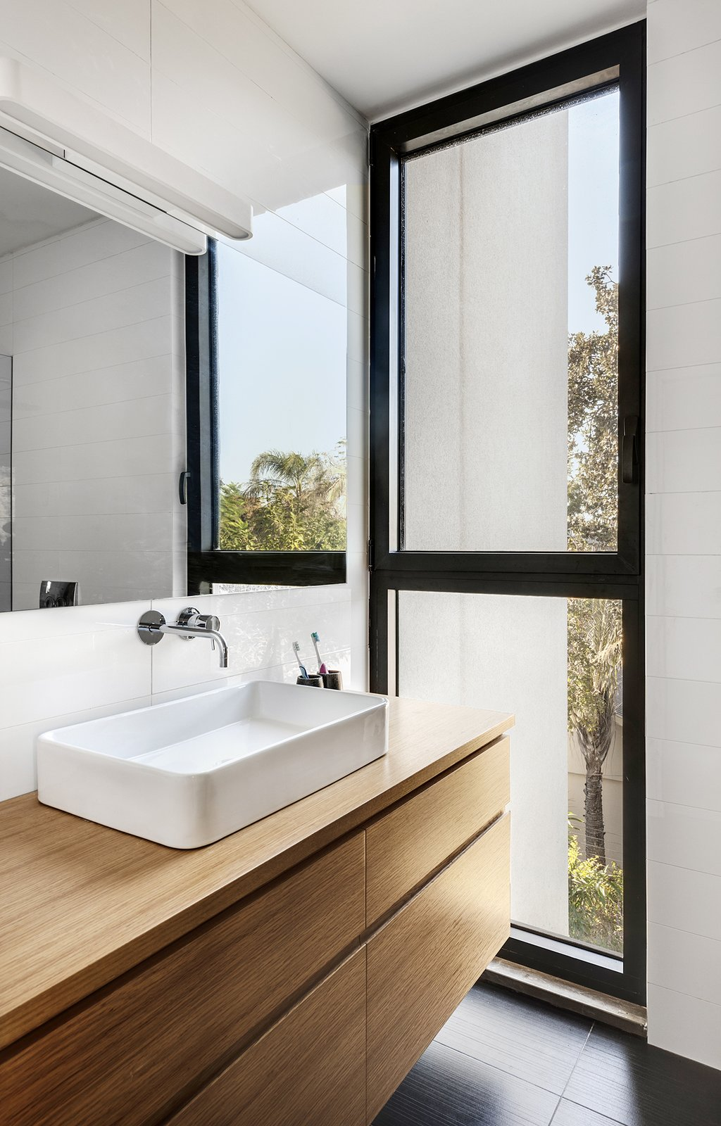 Bath Room, Porcelain Tile Floor, Vessel Sink, and Wood Counter Ravit Dvir Architecture and Design  The House in Harutzim