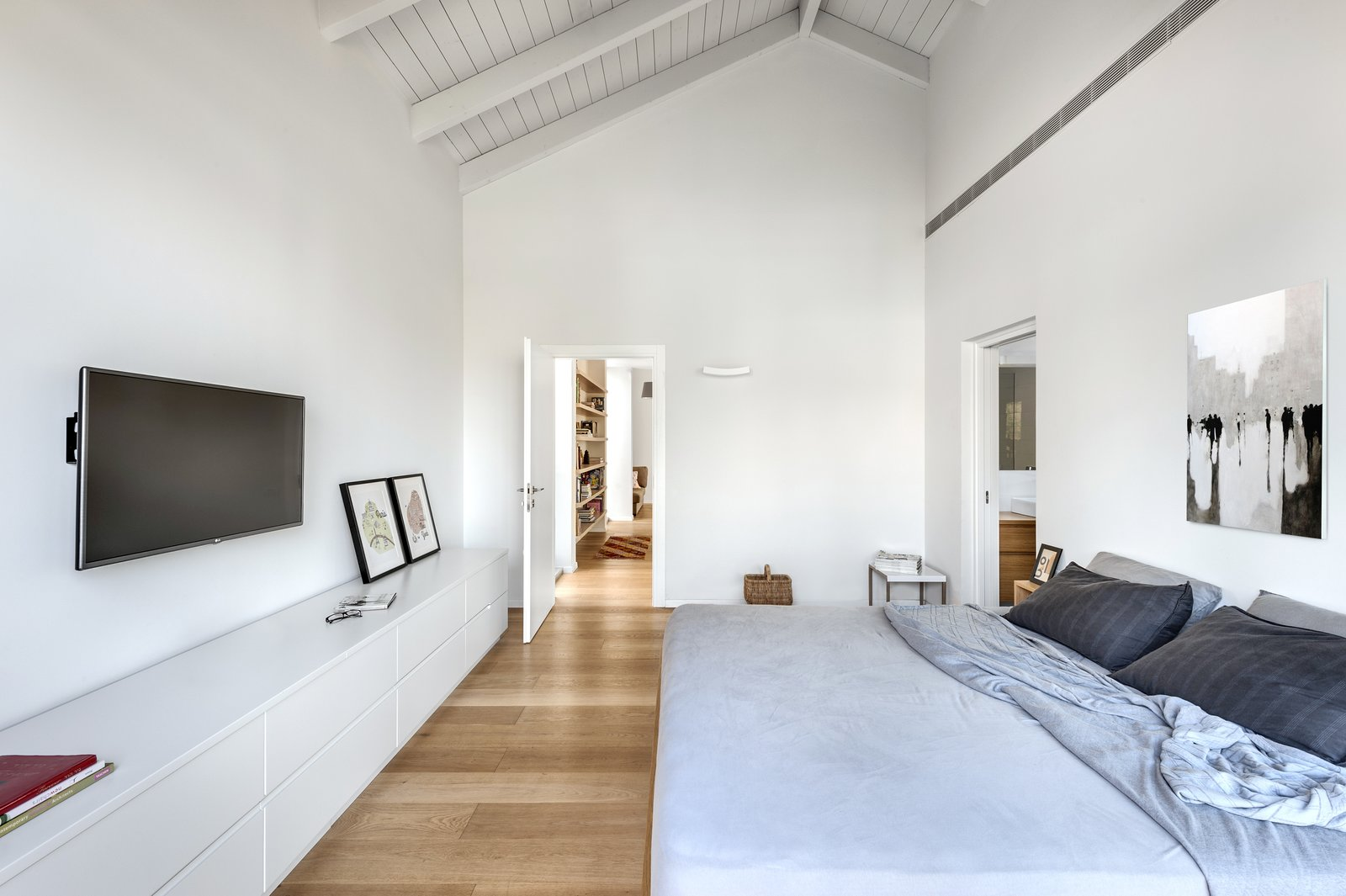 Bedroom, Bed, Light Hardwood Floor, Wall Lighting, and Shelves Ravit Dvir Architecture and Design  The House in Harutzim