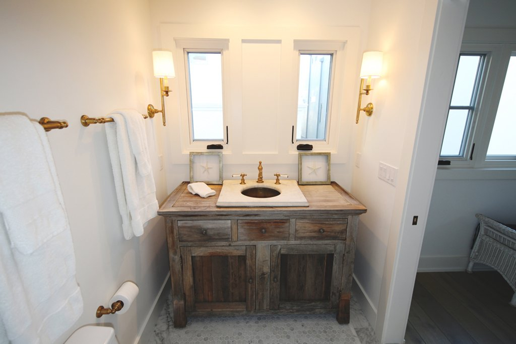 Vintage marble sink and brass lanterns complete this very special beach house getaway bathroom.  Streamlined Cape Cod at The Wedge