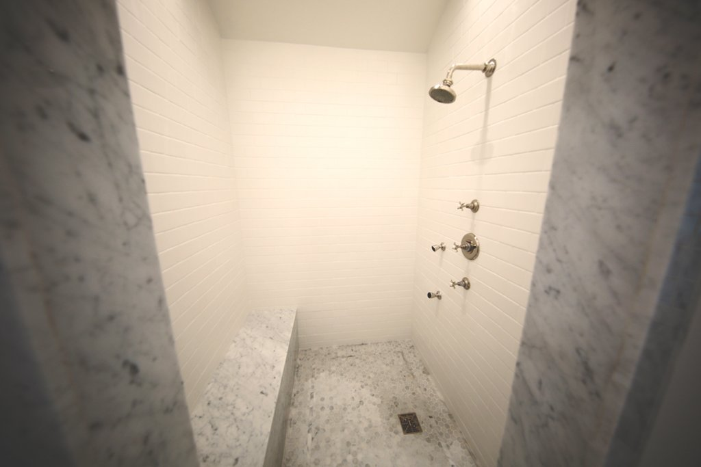 1920s inspired walk in shower with marble trim and seats.   Streamlined Cape Cod at The Wedge
