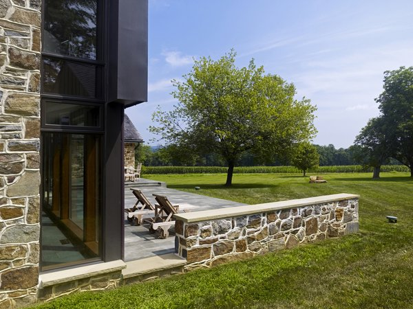 A new stone patio connects living spaces to the rural site beyond.