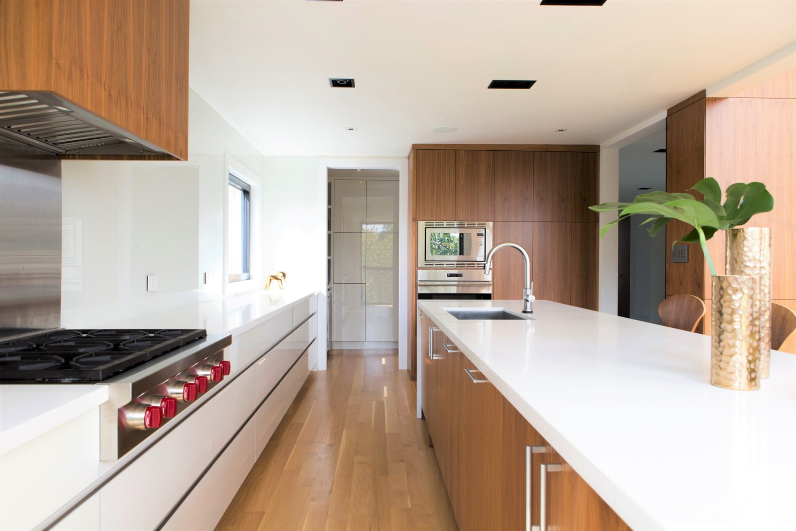 The design of the kitchen is unique in that is has no upper cabinets, and features drawers all throughout the bottom cabinetry – a feature not typically found in residential kitchen designs.  Ravine House by FrankFranco Architects