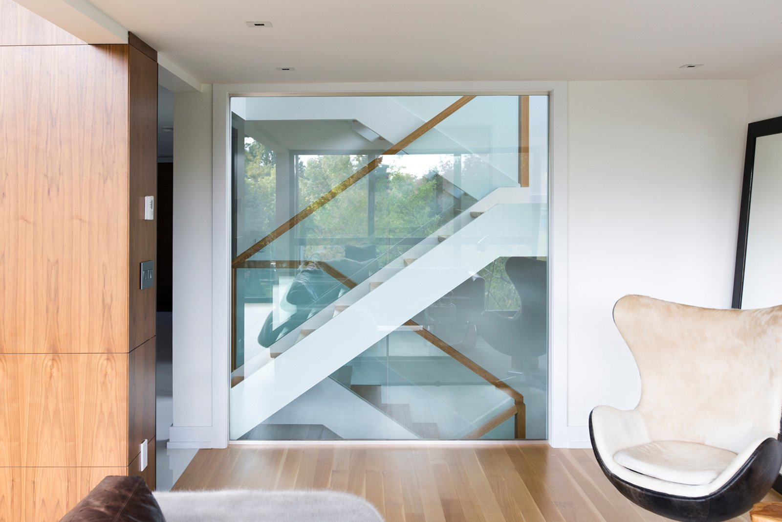 Beyond the custom glass wall in the family room is an open riser oak staircase, with glass guards and a wood handrail.  Ravine House by FrankFranco Architects