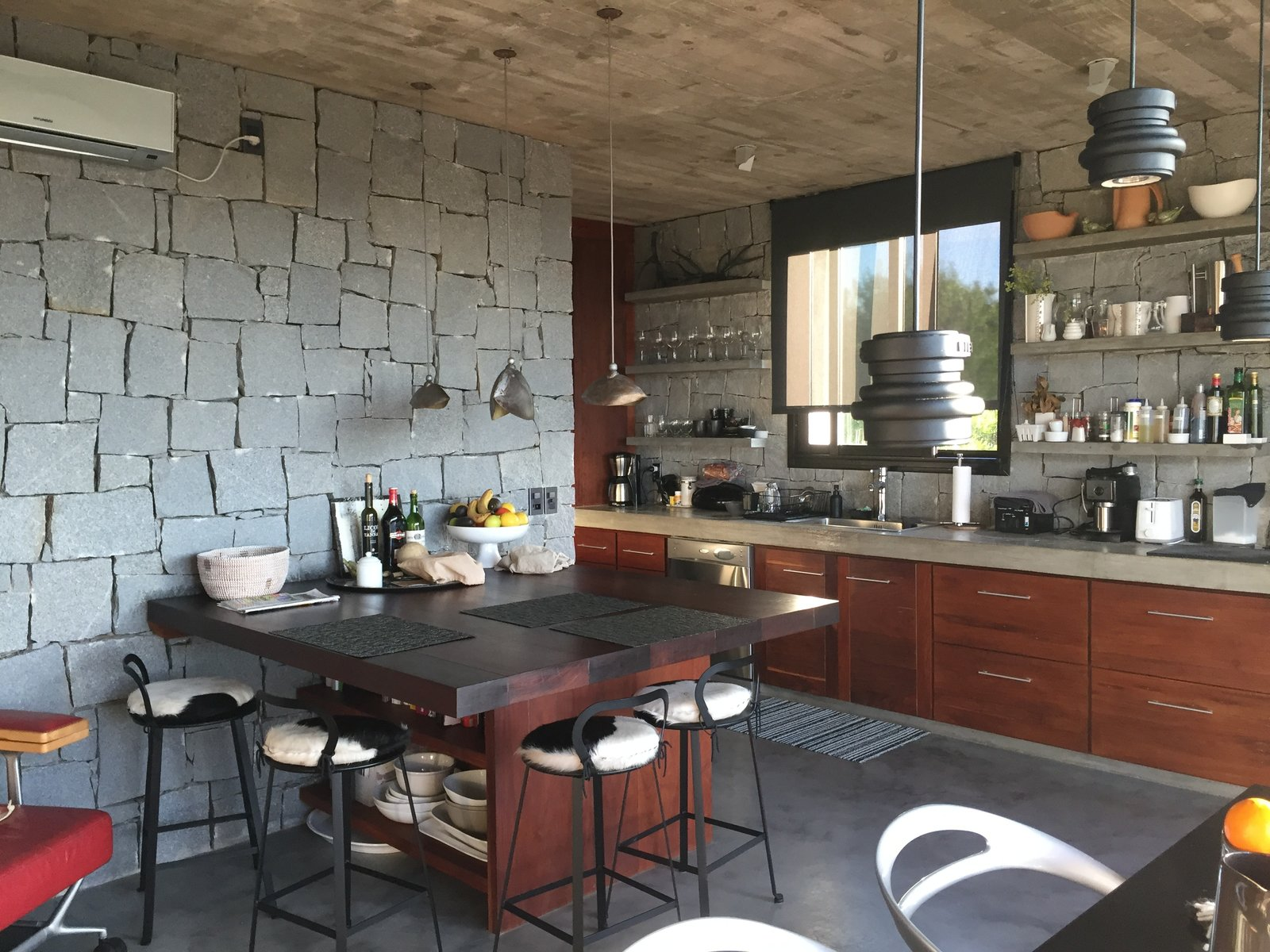 Kitchen, Wine Cooler, Microwave, Refrigerator, Accent Lighting, Concrete Floor, Drop In Sink, Concrete Counter, Dishwasher, Ceiling Lighting, Pendant Lighting, Cooktops, Wood Cabinet, Open Cabinet, Range Hood, and Stone Slab Backsplashe Kitchen  Casa Sienna by Robert Jaye