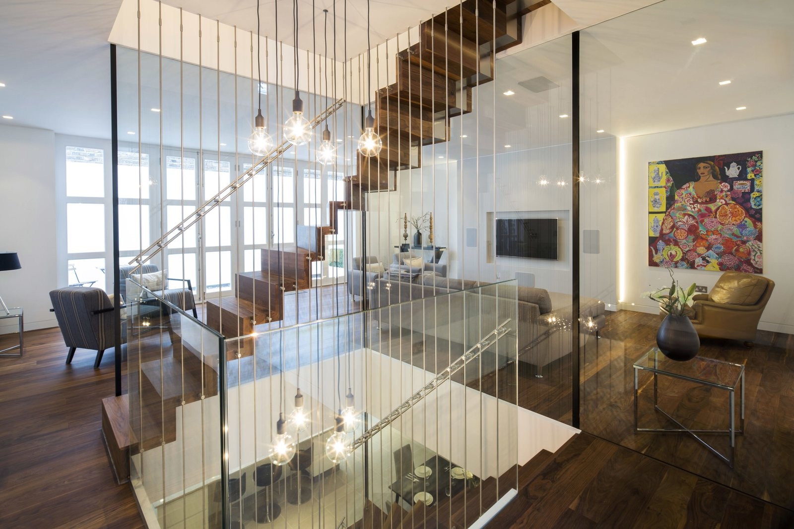 Staircase, Wood Tread, and Metal Railing The project involved the redevelopment of an existing property in St John's Wood. As part of the works a new basement was constructed to the plan area of the property along with remodelling of internal space to create large open areas at ground floor. A new two storey feature stair to link the basement to first floors.  Architect / Designer: Neil Tomlinson Architects PhotographyAgnese Sanvito  Woronzo Road
