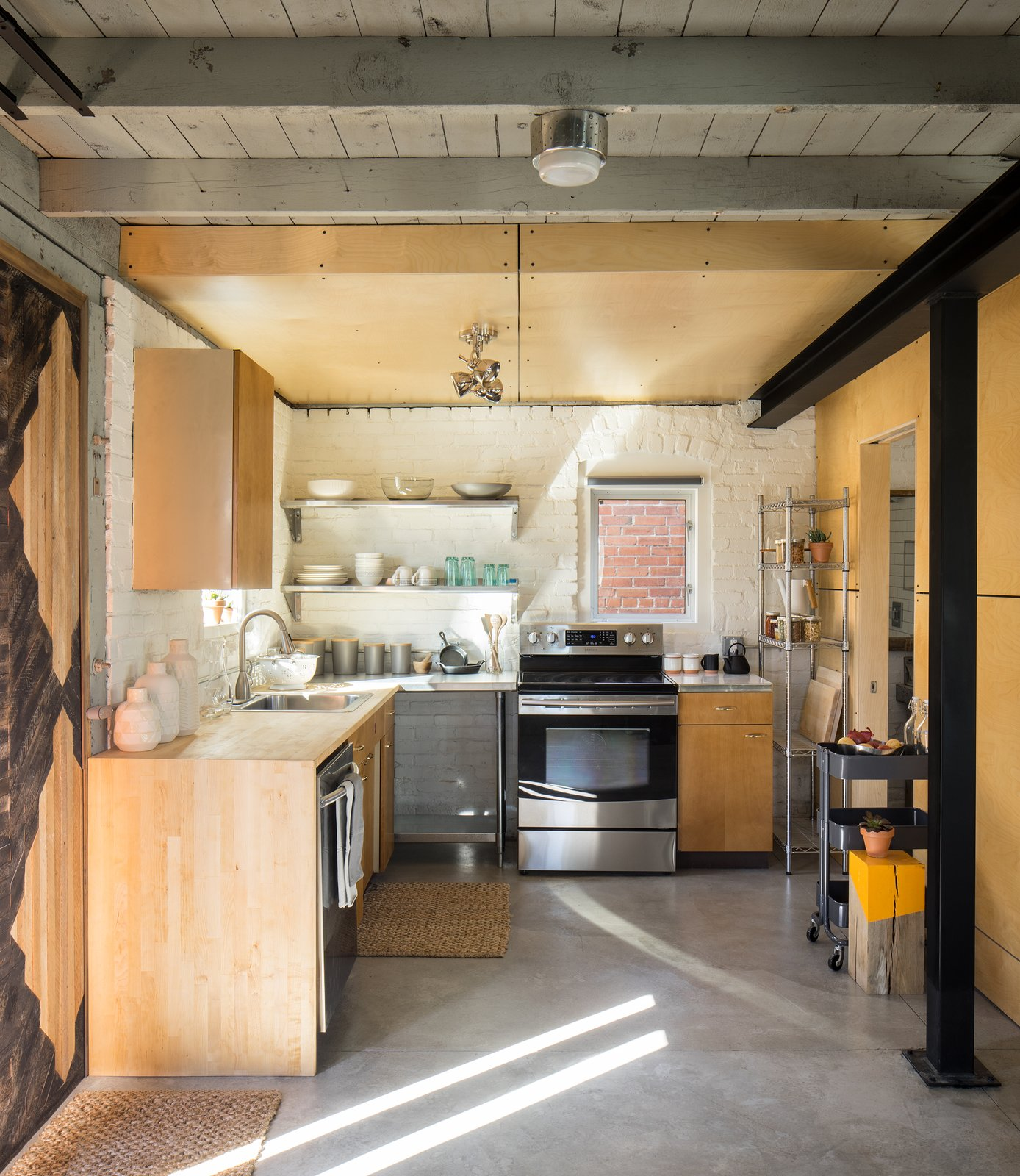 Kitchen, Wood, Metal, Concrete, Brick, Ceiling, Range, Dishwasher, and Drop In Kitchen Area with lath wall panel. Reuse of kitchen cabinets from a 1950's ranch home. Baltic birch wall and ceiling panels.   Best Kitchen Wood Brick Photos from Blacksmith Shop