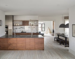 Kitchen, Dining and Living Area. Custom walnut and stainless steel cabinets, engineered quartz tops, marble backsplash, and floating shelves.