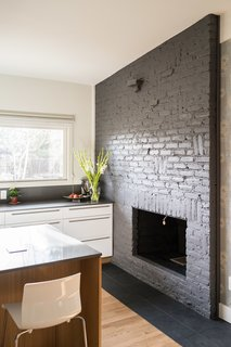 Kitchen fireplace. Original brick was damaged so it was painted dark grey. New slate hearth was added. High gloss Ikea lower cabinets are wrapped with custom white oak panels by AvenueTwo:Design.